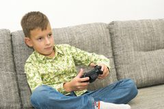 Boy playing video games with joystic sitting on sofa. Boy playing video games with joystic sitting on the sofa Stock Images
