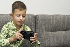 Boy playing video games with joystic sitting on sofa. Boy playing video games with joystic sitting on the sofa Royalty Free Stock Photography