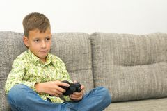 Boy playing video games with joystic sitting on sofa. Boy playing video games with joystic sitting on the sofa Royalty Free Stock Images
