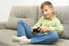Boy playing video games with joystic sitting on sofa. Boy playing video games with joystic sitting on the sofa Royalty Free Stock Photo