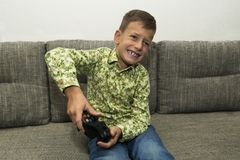Boy playing video games with joystic sitting on sofa. Boy playing video games with joystic sitting on the sofa Royalty Free Stock Photos