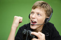 Boy Playing Video Games - WIN. Teenage boy playing video games, with headphones on his head, wining the game. success, fist in the air. Holding joystick Stock Photography