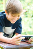 Boy playing video games. Young boy playing video games outdoors Stock Photography