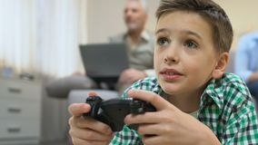 Boy playing videogame, grandpa using laptop on background, lack of communication