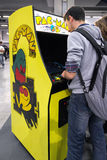 Boy playing with vintage Pac Man at Games Week 2015. MILAN, ITALY - OCTOBER 25: Boy playing with vintage Pac Man at Games Week 2015, event dedicated to video Stock Photos