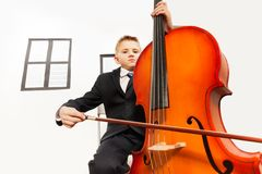 Boy playing violoncello sitting on the chair Stock Image