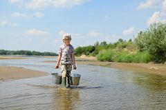 The boy is playing with water on the banks of the river. During a warm summer. Carries two buckets. Children`s fun in the water. Holidays time stock photos