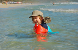 Boy playing in the water. A child plays in the waves at the beach Stock Images