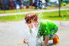 Boy playing in water fountain. Young boy putting his face in water fountain in park Stock Photos