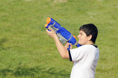 Boy playing with water gun. Adorable twelve year old boy playing with water gun outside in grass stock photos