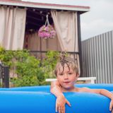 Cheerful children playing in water. Water pool on front, back yard. Children and nature. Summer time. Traveling concept. Vacation. Boy playing in water pool stock photography