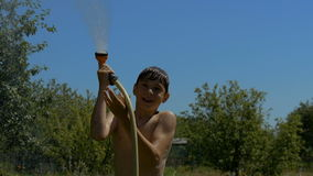 Boy playing with water on a sunny day. Child playing with water on a sunny day. Very fun and beautiful stock footage