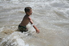 Boy Playing in Water Stock Images