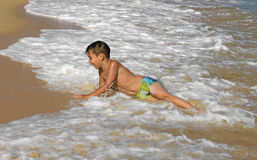 Boy playing in the waves Stock Image