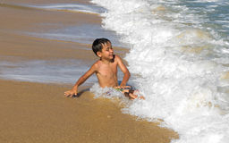 Boy playing in the waves Royalty Free Stock Image