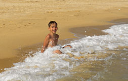Boy playing in the waves Stock Photos
