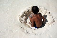 Boy playing in the white sand Stock Photos