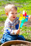 Boy Playing With Wind Toy. A one year old boy plays with a whirligig propeller pinwheel outside while wearing a striped shirt Stock Photo