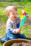 Boy Playing With Wind Toy. A one year old boy plays with a whirligig propeller pinwheel outside while wearing a striped shirt Stock Photography