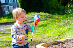 Boy Playing With Wind Toy. A one year old boy plays with a whirligig propeller pinwheel outside while wearing a striped shirt Stock Images