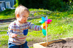 Boy Playing With Wind Toy. A one year old boy plays with a whirligig propeller pinwheel outside while wearing a striped shirt Royalty Free Stock Photo