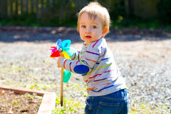 Boy Playing With Wind Toy. A one year old boy plays with a whirligig propeller pinwheel outside while wearing a striped shirt Royalty Free Stock Photography