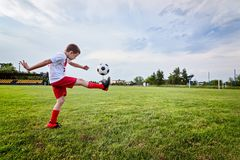 Boy Playing With Football Ball On Playing Field. Stock Photos