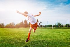 Boy Playing With Football Ball On Playing Field. Stock Photo