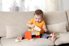 Boy playing with wooden building toys at home Royalty Free Stock Images