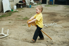 Boy playing with wooden horse Stock Image