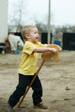 Boy playing with wooden horse Stock Photos