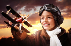 Boy playing with wooden toy airplane. Boy wearing old-fashioned aviator hat, scarf and goggles holding a wooden biplane up in the air with sunset royalty free stock photos
