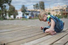 Boy playing on a wooden walkway on the beach Royalty Free Stock Photo