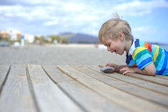 Boy playing on a wooden walkway on the beach Stock Photo