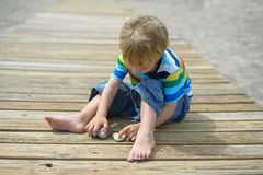 Boy playing on a wooden walkway on the beach Stock Photography