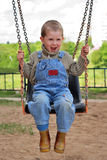 Boy is playng on the swings Royalty Free Stock Images