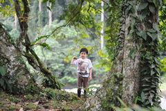 A boy playing in a tropical forest in Borneo Danum Valley reserve Royalty Free Stock Photography