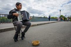 Boy plays the accordion on Paris bridge over the Seine Royalty Free Stock Image