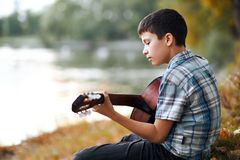 The boy plays an acoustic guitar, sits on the Bank of the river, autumn forest at sunset, beautiful nature and the reflection of t. Rees in the water stock photos