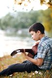 The boy plays an acoustic guitar, sits on the Bank of the river, autumn forest at sunset, beautiful nature and the reflection of t. Rees in the water royalty free stock image