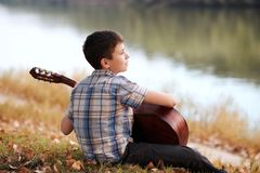 The boy plays an acoustic guitar, sits on the Bank of the river, autumn forest at sunset, beautiful nature and the reflection of t. Rees in the water royalty free stock photography