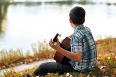 The boy plays an acoustic guitar, sits on the Bank of the river, autumn forest at sunset, beautiful nature and the reflection of t. Rees in the water royalty free stock photos