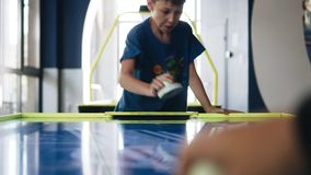 The boy plays air hockey with his father. View along the game table. Entertainment. Communication. Family stock footage