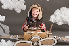 The boy plays in an airplane made of cardboard box and dreams of becoming a pilot, clouds of cotton wool on a gray background royalty free stock photo