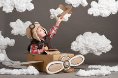 The boy plays in an airplane made of cardboard box and dreams of becoming a pilot, clouds of cotton wool on a gray background royalty free stock photography