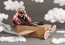 The boy plays in an airplane made of cardboard box and dreams of becoming a pilot, clouds of cotton wool on a gray background royalty free stock photos
