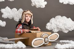 The boy plays in an airplane made of cardboard box and dreams of becoming a pilot, clouds of cotton wool on a gray background royalty free stock image