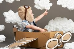 The boy plays in an airplane made of cardboard box and dreams of becoming a pilot, clouds from cotton wool on a gray background, r stock image