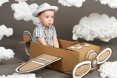 The boy plays in an airplane made of cardboard box and dreams of becoming a pilot, clouds from cotton wool on a gray background, r royalty free stock photo
