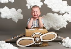 The boy plays in an airplane made of cardboard box and dreams of becoming a pilot, clouds from cotton wool on a gray background, r royalty free stock images
